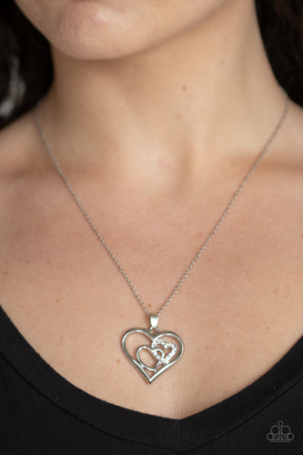 A white rhinestone encrusted heart intertwines with a plain silver heart inside of a larger silver heart frame, creating a romantic pendant at the bottom of a shimmery silver chain. Features an adjustable clasp closure.  Sold as one individual necklace. Includes one pair of matching earrings. Always nickel and lead free.