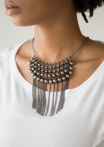 Gradually increasing in size, glistening gunmetal beads swing from a net of interlocking gunmetal links. Shimmery gunmetal chains stream from the bottom of the beaded fringe for an edgy finish. Features an adjustable clasp closure.  Sold as one individual necklace. Includes one pair of matching earrings.  Always nickel and lead free.