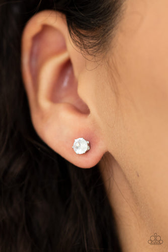 A classic white cubic zirconia is pressed into the center of a sleek silver frame for a timeless look. Earring attaches to a standard post fitting. Features a daintier design to accommodate multiple ear piercings.  Sold as one pair of post earrings.  Always nickel and lead free.