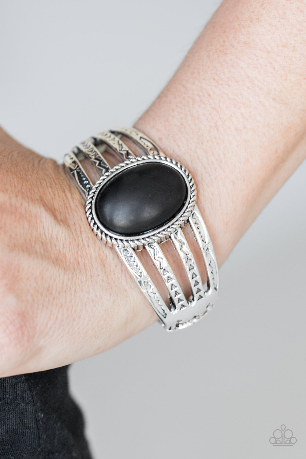 Stamped in tribal glyph-like patterns, glistening silver bars arc across the wrist, coalescing into a bold cuff-like bracelet. An earthy black stone is pressed into the center of the piece for a seasonal finish. Features a hinged closure.  Sold as one individual bracelet.  Always nickel and lead free.