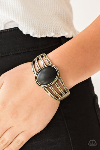 Stamped in tribal glyph-like patterns, glistening brass bars arc across the wrist, coalescing into a bold cuff-like bracelet. An earthy black stone is pressed into the center of the piece for a seasonal finish. Features a hinged closure.  Sold as one individual bracelet.   Always nickel and lead free.