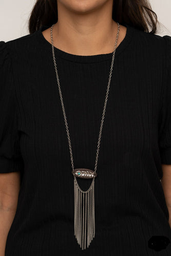 A fringe of silver chains swings from the bottom of a wooden frame adorned with a shimmery silver feather charm. Dotted with a refreshing turquoise stone, the whimsical pendant attaches to a lengthened silver chain for a free-spirited finish. Features an adjustable clasp closure.  Sold as one individual necklace. Includes one pair of matching earrings.  Always nickel and lead free.