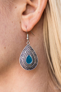 Painted in a blue center, an ornate teardrop embossed in tribal inspired textures swings from the ear in an indigenous fashion. Earring attaches to a standard fishhook fitting.  Sold as one pair of earrings.  Always nickel and lead free.