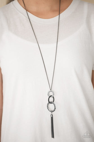Delicately hammered in glistening textures, shimmery gunmetal hoops swing from the bottom of a shiny gunmetal chain, creating a bold industrial pendant. A shimmery gunmetal tassel swings from the bottom of the stacked pendant for a seasonal finish. Features an adjustable clasp closure.  Sold as one individual necklace. Includes one pair of matching earrings.  Always nickel and lead free.