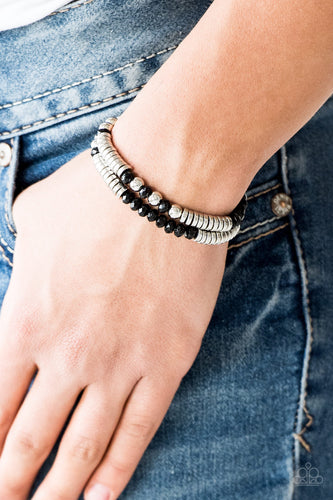 Classic silver beads, faceted black crystal-like beads, and dainty silver discs are threaded along stretchy bands, creating shimmery layers across the wrist.  Sold as one set of two bracelets.  Always nickel and lead free.