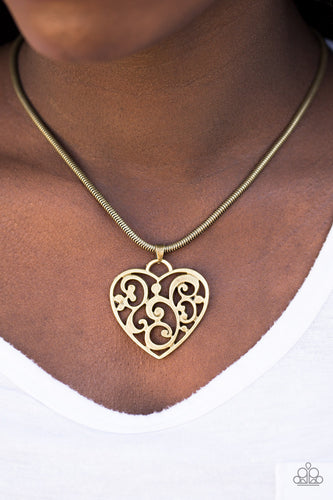 An airy heart swings from the bottom of a shimmery brass cocoon chain, creating a whimsical pendant below the collar. Brushed in an antiqued shimmer, frilly filigree climbs the heart frame for a vintage inspired finish. Features an adjustable clasp closure.  Sold as one individual necklace. Includes one pair of matching earrings.    Always nickel and lead free.