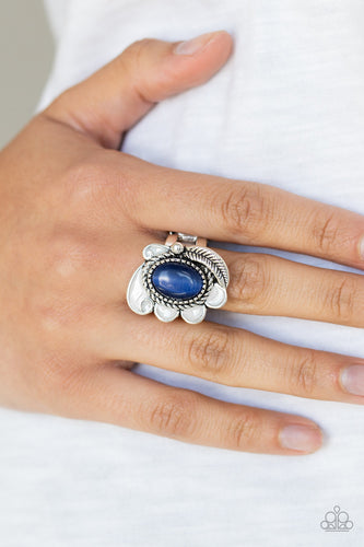 A glowing blue cat's eye stone is pressed into the center of a shimmery silver frame radiating with a silver feather and glistening white petals, creating a whimsical compilation atop the finger. Features a stretchy band for a flexible fit.  Sold as one individual ring.  Always nickel and lead free.