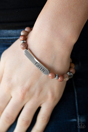 A collection of multicolored stones, dainty silver beads, and a silver plate stamped with the inspirational word,