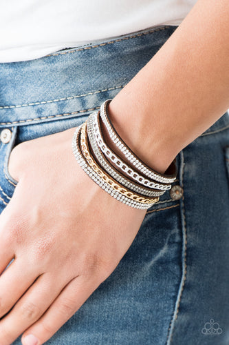 Glassy white and smoky rhinestones are encrusted along strands of brown suede. Glistening silver and gold chains are added to the bands, adding edgy industrial shimmer to the sassy palette. Features an adjustable snap closure.  Sold as one individual bracelet.  Always nickel and lead free.