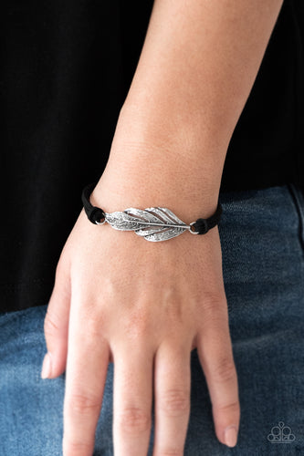Strands of black suede knot around a shimmery silver feather charm, creating a seasonal pendant atop the wrist. Features an adjustable clasp closure.  Sold as one individual bracelet.  Always nickel and lead free.