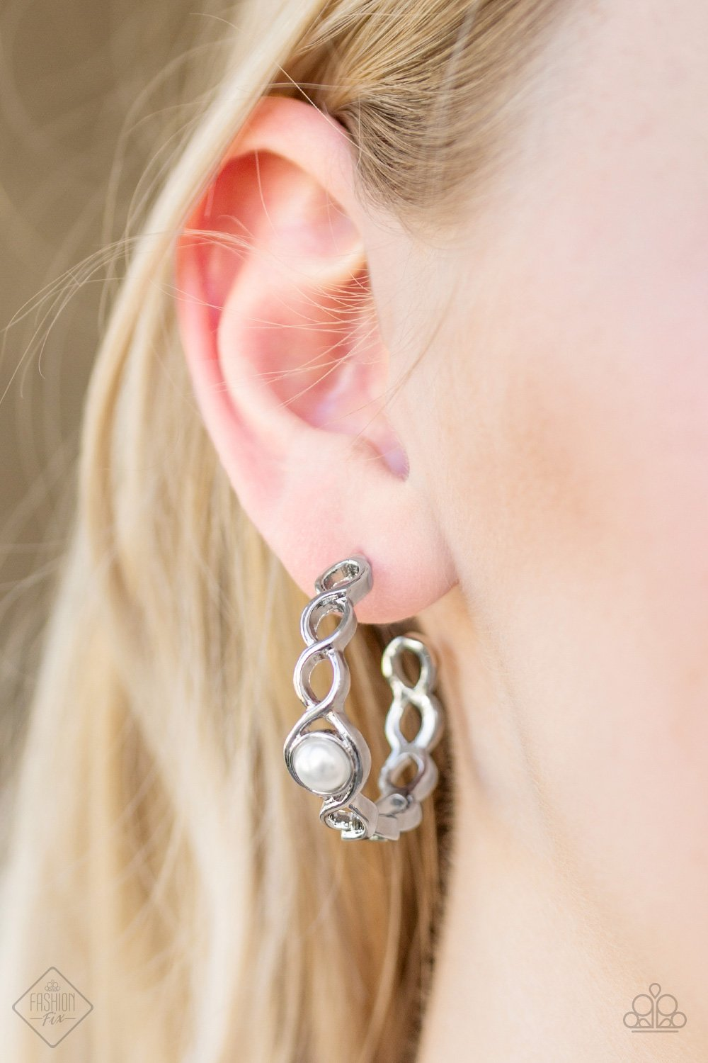 Glistening silver bars weave around a white pearl-drop center, creating a refined hoop. Earring attaches to a standard post fitting. Hoop measures 1