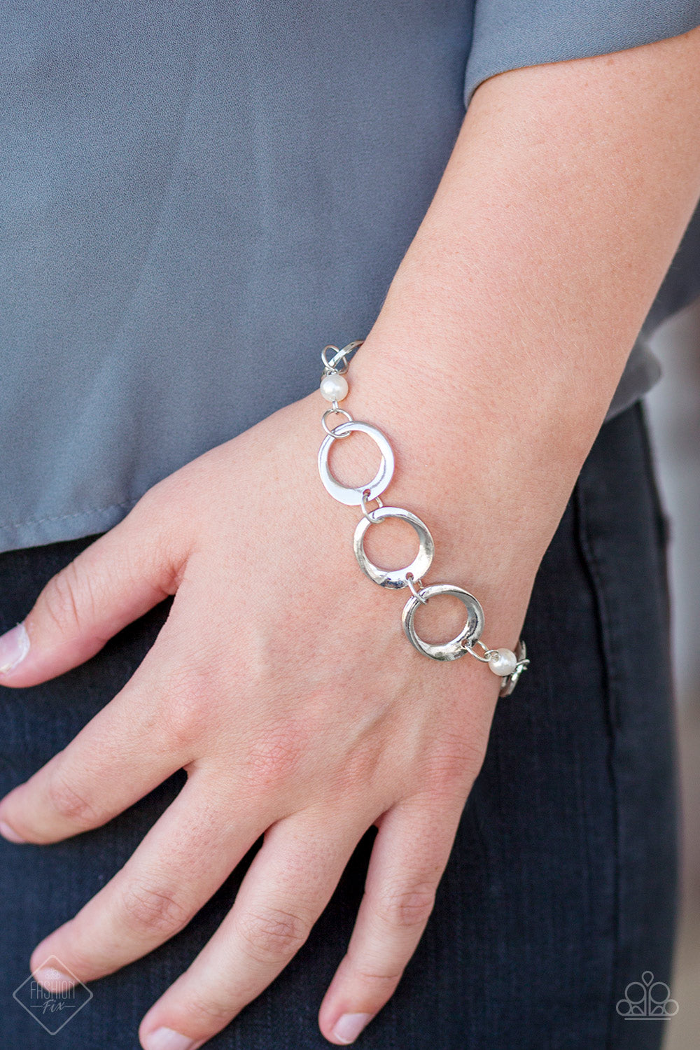 Asymmetrical silver hoops connect with pearly white beads across the wrist for a refined look. Features an adjustable clasp closure.  Sold as one individual bracelet.  Always nickel and lead free.
