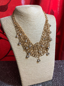 A collar of layered interlocking gold chain provides the canvas for gorgeous clear rhinestones to sway delicately. Features an adjustable clasp closure.  Sold as one individual necklace. includes one pair of marching earrings.  Always nickel and lead free.