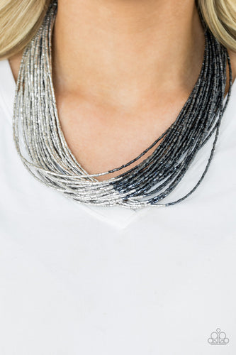 Brushed in a flashy metallic finish, countless strands of blue seed beads converge with strands of silver seed beads, creating colorful layers below the collar. Features an adjustable clasp closure.  Sold as one individual necklace. Includes one pair of matching earrings.  Always nickel and lead free.
