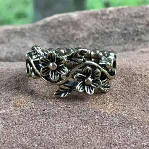 Shimmery brass flowers create a whimsical band across the finger. Features a dainty stretchy band for a flexible fit.  Sold as one individual ring.  Always nickel and lead free.