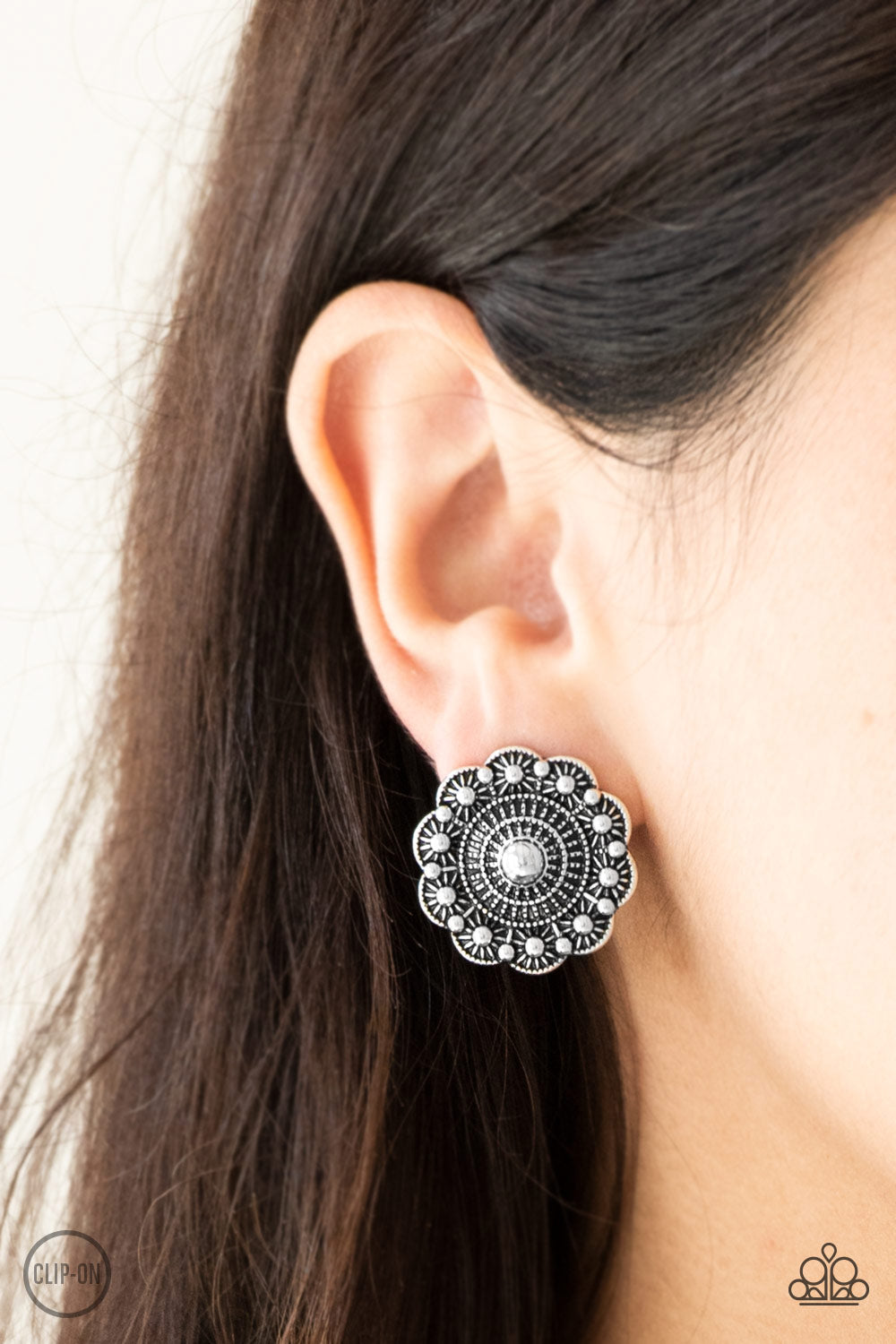 Brushed in an antiqued shimmer, a studded silver floral frame radiates with rippling textures for a seasonal fashion. Earring attaches to a standard clip-on fitting.  Sold as one pair of clip-on earrings.  Always nickel and lead free.