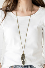 Load image into Gallery viewer, Featuring studded and antiqued textures, a dramatic brass feather pendant swings from the bottom of an elongated brass chain for a free-spirited fashion. Features an adjustable clasp closure.  Sold as one individual necklace. Includes one pair of matching earrings.   Always nickel and lead free.