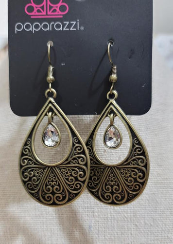 A white rhinestone swings from the top of a brass teardrop frame radiating with filigree textures for a refined look. Earring attaches to a standard fishhook fitting.  Sold as one pair of earrings.  Always nickel and lead free.  Fashion Fix January 2021
