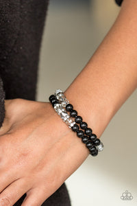 Faceted crystal-like beads and shiny black beads are threaded along stretchy elastic strands, creating radiant layers across the wrist. Encrusted in dazzling white rhinestones, dainty silver rings are sprinkled between one row of crystal-like beads for a refined finish.  Sold as one set of two bracelets.  Always nickel and lead free.