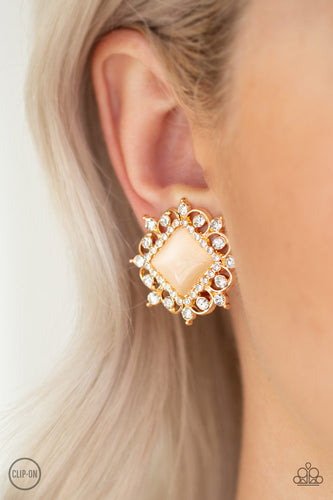 Featuring a regal square cut, a glowing peach moonstone is pressed into the center of an ornate gold frame radiating with glassy white rhinestones for a timeless look. Earring attaches to a standard clip-on fitting.  Sold as one pair of clip-on earrings.  Always nickel and lead free.