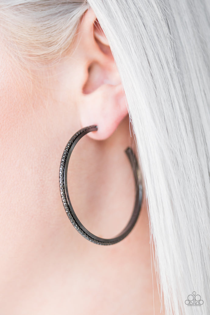 Etched in diamond cut textures, a shimmery gunmetal hoop curls around a smooth gunmetal frame, coalescing into an edgy hoop. Earring attaches to a standard post fitting. Hoop measures 2