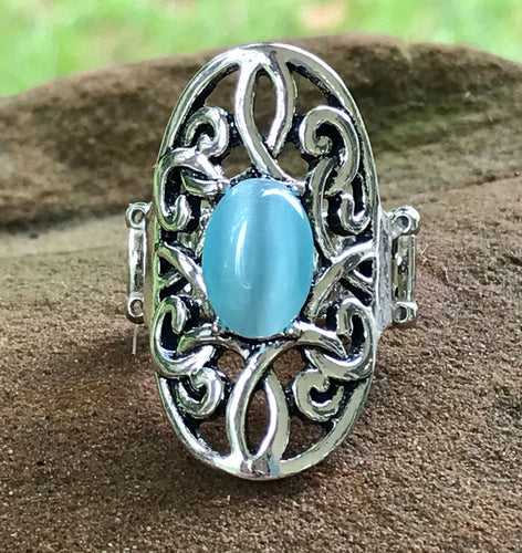 A glowing blue cat's eye stone is pressed into the center of an oval backdrop swirling with vine-like filigree for a whimsical look. Features a stretchy band for a flexible fit.  Sold as one individual ring.  Always nickel and lead free.   Fashion Fix Exclusive July 2020