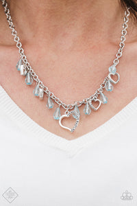Crystal-like teardrops in the refreshing shade of Blue Radiance drip from the bottom of a shimmery silver chain. Stamped in ornate patterns, glistening silver heart silhouettes trickle between the colorful accents, creating a whimsical fringe below the collar. Features an adjustable clas