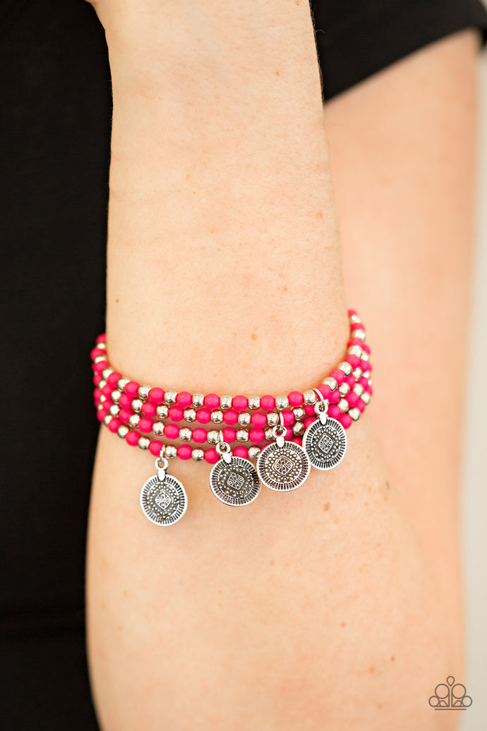 Dainty pink and silver beads are threaded along stretchy elastic bands, creating colorful layers across the wrist. Brushed in an antiqued shimmer, ornate silver charms swing from the wrist for a wanderlust finish.  Sold as one set of four bracelets.  Always nickel and lead free.