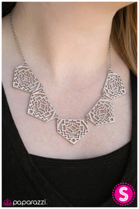 Shimmery metallic plates swing from a classic silver chain, creating a geometric fringe. Decorated in a Southwestern textile pattern, the stenciled plates fall just below the collar in an airy fashion. Features an adjustable clasp closure.  Sold as one individual necklace. Includes one pair of matching earrings.  Always nickel and lead free.