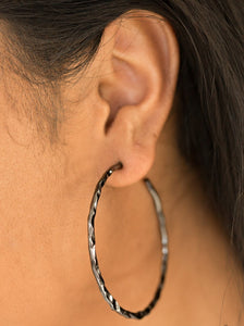 "Brushed in a high-sheen finish, a glistening gunmetal hoop has been delicately hammered for an edgy finish. Earring attaches to a standard post fitting. Hoop measures 2"" in diameter.  Sold as one pair of hoop earrings.  Always nickel and lead free."