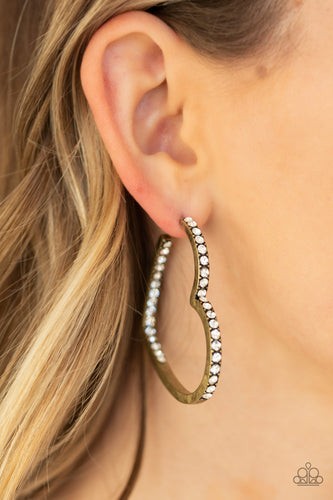 Encrusted in sections of glittery white rhinestones, a glistening brass hoop curls into a charming heart shape for a heart-stopping look. Earring attaches to a standard post fitting. Hoop measures approximately 2