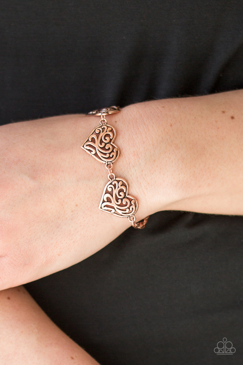 Featuring filigree-filled centers, glistening copper heart frames connect around the wrist in a romantic fashion. Features an adjustable clasp closure.  Sold as one individual bracelet..  Always nickel and lead free.