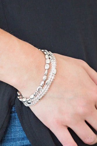 Infused with hints of silver, dainty white crystal-like beads are threaded along stretchy bands, creating whimsical layers across the wrist.  Sold as one set of three bracelets.  Always nickel and lead free