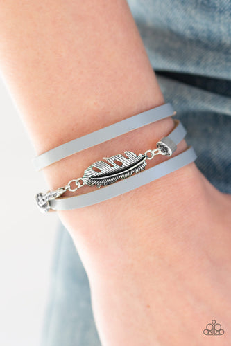 Infused with a shimmery silver feather charm, an elongated strip of gray leather triple wraps around the wrist for a wanderlust flair. Features a clasp closure.  Sold as one individual bracelet.  Always nickel and lead free.