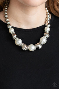 A collection of oversized white pearls, silver rings, and asymmetrical silver beads are threaded along an invisible wire below the collar. White rhinestone encrusted rings are sprinkled between the refined beading for a statement-making finish. Features an adjustable clasp closure.  Sold as one individual necklace. Includes one pair of matching earrings.  Always nickel and lead free.