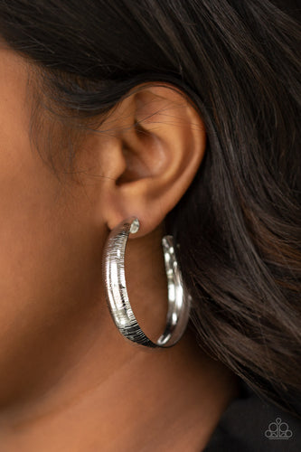 Etched in a shimmery linear pattern, a thick silver hoop curls around the ear for some classic edge. Earring attaches to a standard post fitting. Hoop measures approximately 2