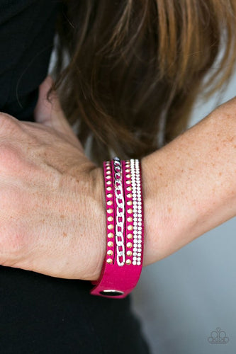 Shiny gold studs, silver chain, and rows of dazzling white rhinestones adorn strands of pink suede, creating endless shimmer across the wrist. Features an adjustable snap closure.  Sold as one individual bracelet.   Always nickel and lead free.