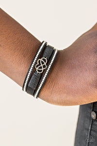 Black leather strands layer across the wrist. Infused with rows of white rhinestones, black cording knots around the centermost strand, securing an airy heart and infinity charm in place for a whimsical finish. Features an adjustable clasp closure.  Sold as one individual bracelet.  Always nickel and lead free.