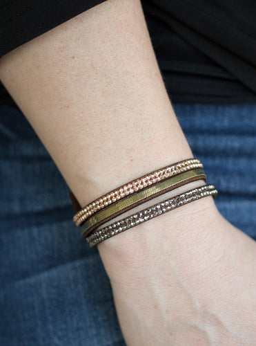 A brown suede band is spliced into three strands featuring rows of glittery hematite rhinestones, flat brass chain, and faceted metallic rhinestones for a glamorous look. Features an adjustable snap closure. Sold as one individual bracelet.  Always nickel and lead free.