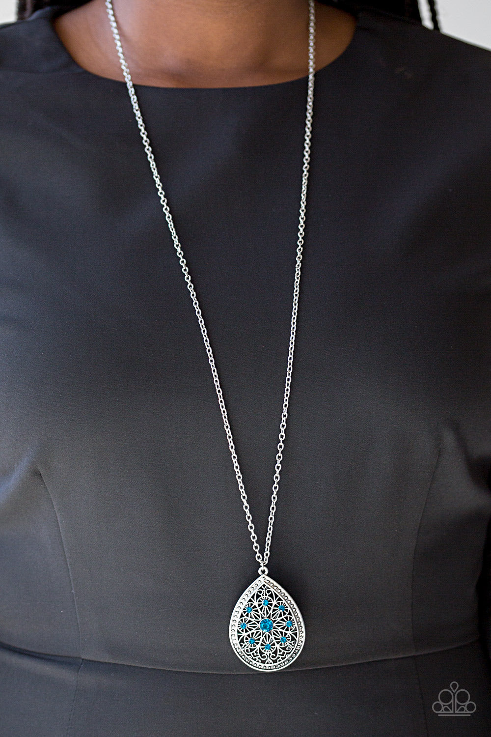 A dramatic teardrop pendant swings from the bottom of an elongated silver chain, elegantly slimming the torso. Glittery blue rhinestones are sprinkled along the pendant as silver filigree dances across the center, creating a regal floral pattern. Features an adjustable clasp closure.  Sold as one individual necklace. Includes one pair of matching earrings.  Always nickel and lead free!