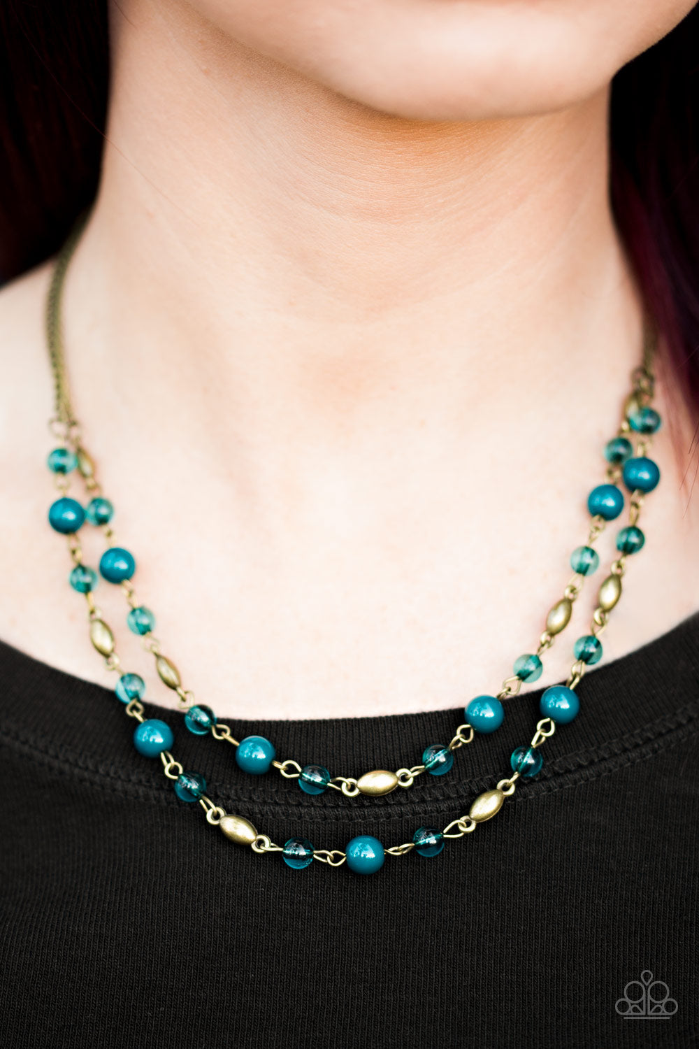 Rustic blue beads trickle along two strands of shimmery brass chain. Infused with shiny brass beading, blue crystal like beads trickle between the colorful accents, creating whimsical layers below the collar. Features an adjustable clasp closure.   Sold as one individual necklace. Includes one pair of matching earrings.   Always nickel and lead free.