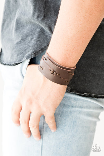 Pieces of brown leather are stitched in place across the front of a thick brown leather band for a rugged look. Features an adjustable snap closure.  Sold as one individual bracelet.  Always nickel and lead free.