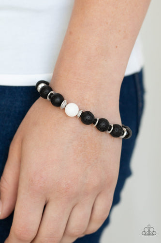 Essential Oil Alert!!  An earthy collection of shiny silver accents, black lava rock beads, and a single white stone bead is threaded along a stretchy band around the wrist for a seasonal flair. Sold as one individual bracelet.  Always nickel and lead free.  Item #P9SE-URWT-074XX