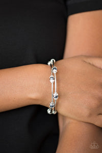Dainty metallic blue crystal-like beads and shimmery silver accents alternate along a coiled wire to create a refined infinity wrap style bracelet.  Sold as one individual bracelet.  Always nickel and lead free.