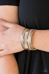 Brushed in a metallic shimmer, strips of brown leather are encrusted in alternating rows of glittery white rhinestones. Brown cording knots around the centermost strand, securing a sparkling heart frame in place for a whimsical finish. Features an adjustable clasp closure.  Sold as one individual bracelet. Always nickel and lead free.