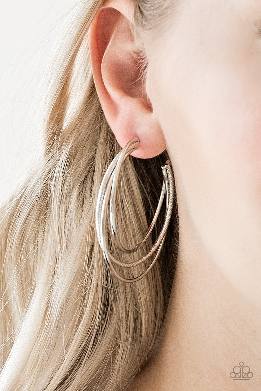 Featuring smooth and serrated finishes, shiny silver frames layer into a bold hoop for a spunky industrial flair. Earring attaches to a standard post fitting. Hoop measures 1 3/4