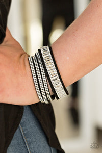 Encrusted in mismatched sparkle, half of a black suede band is encrusted in white emerald style cut rhinestones, while the other half splits into three separate bands encrusted in white rhinestones for a sassy look. The elongated band allows for a trendy double wrap design. Features an adjustable snap closure.  Sold as one individual bracelet.  Always nickel and lead free.