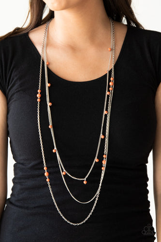 Infused with a plain silver chain, mismatched orange stone beads sporadically trickle along shimmery silver chains, creating vivacious layers down the chest. Features an adjustable clasp closure.  Sold as one individual necklace. Includes one pair of matching earrings. Always nickel and lead free.