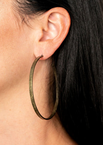 An antiqued brass hoop curls into an exaggerated curve for a rustic finish. Earring attaches to a standard post fitting. Hoop measures approximately 2 3/4