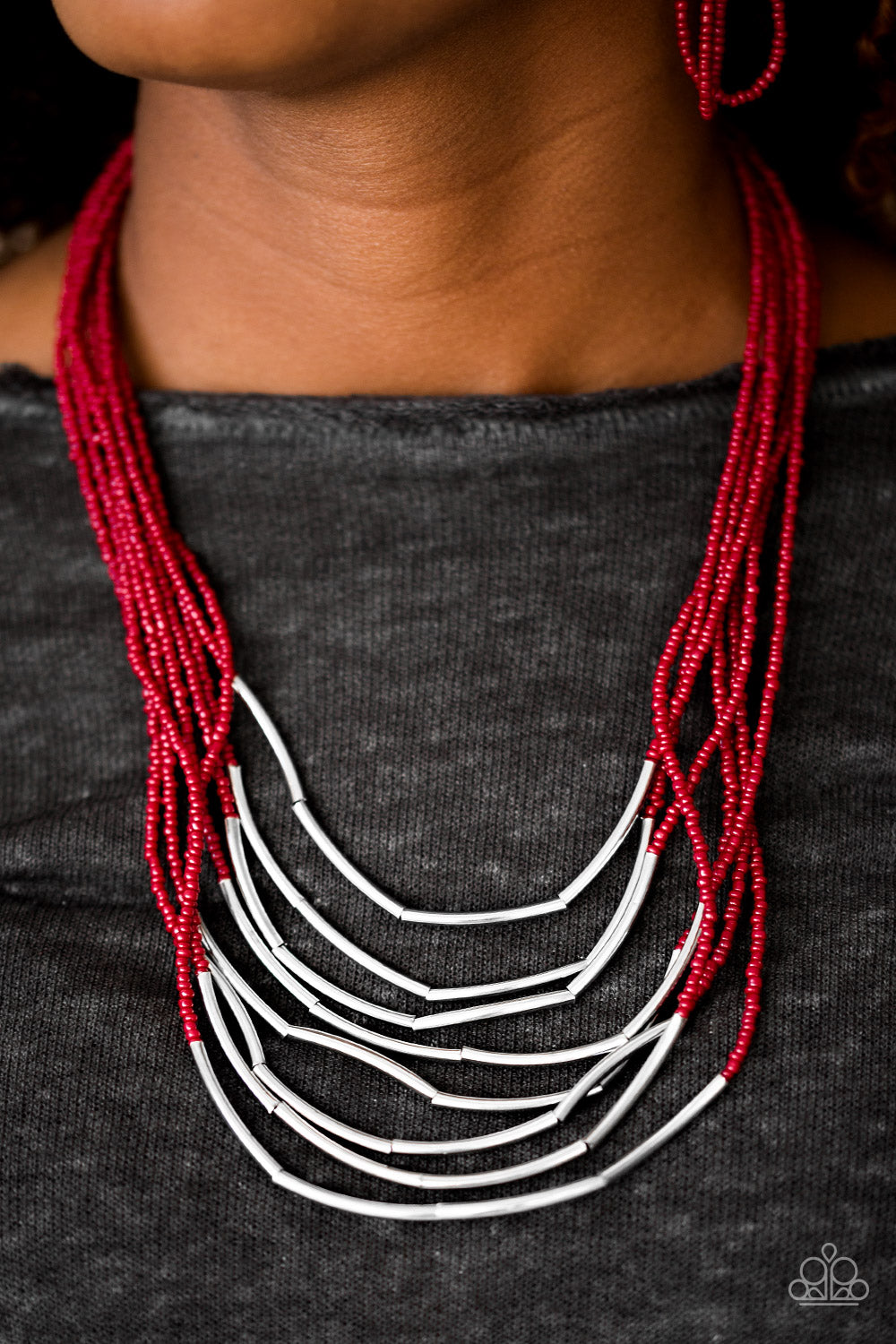 Infused with two large silver fittings, shiny red seed beads are threaded along countless strands, creating dramatic layers below the collar. Shimmery silver accents slide along the centers of the strands, adding depth and shimmer to the seasonal palette. Features an adjustable clasp closure.  Sold as one individual necklace. Includes one pair of matching earrings.   Always nickel and lead free!